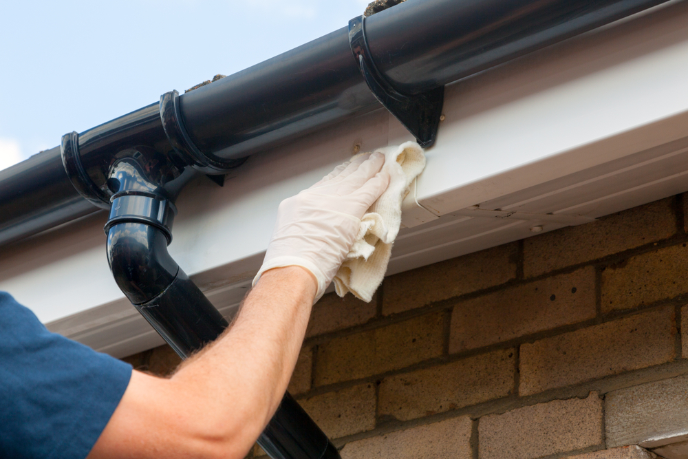 plumber-wiping-down-house-gutter